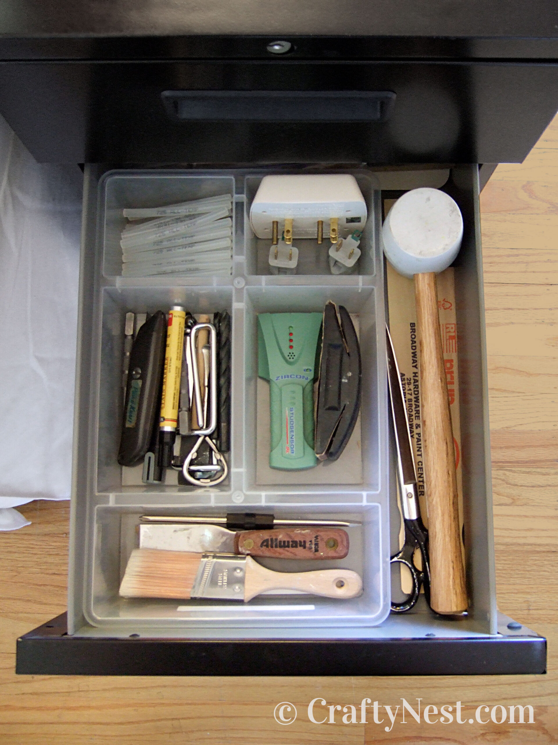 Onpen file cabinet drawer with tools organized inside, photo