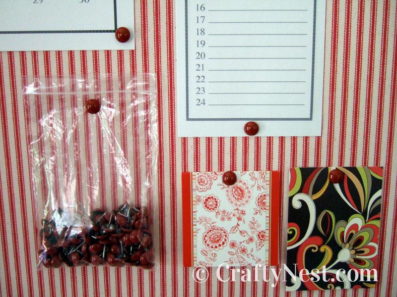 Red upholstery tacks used as thumbtacks, photo