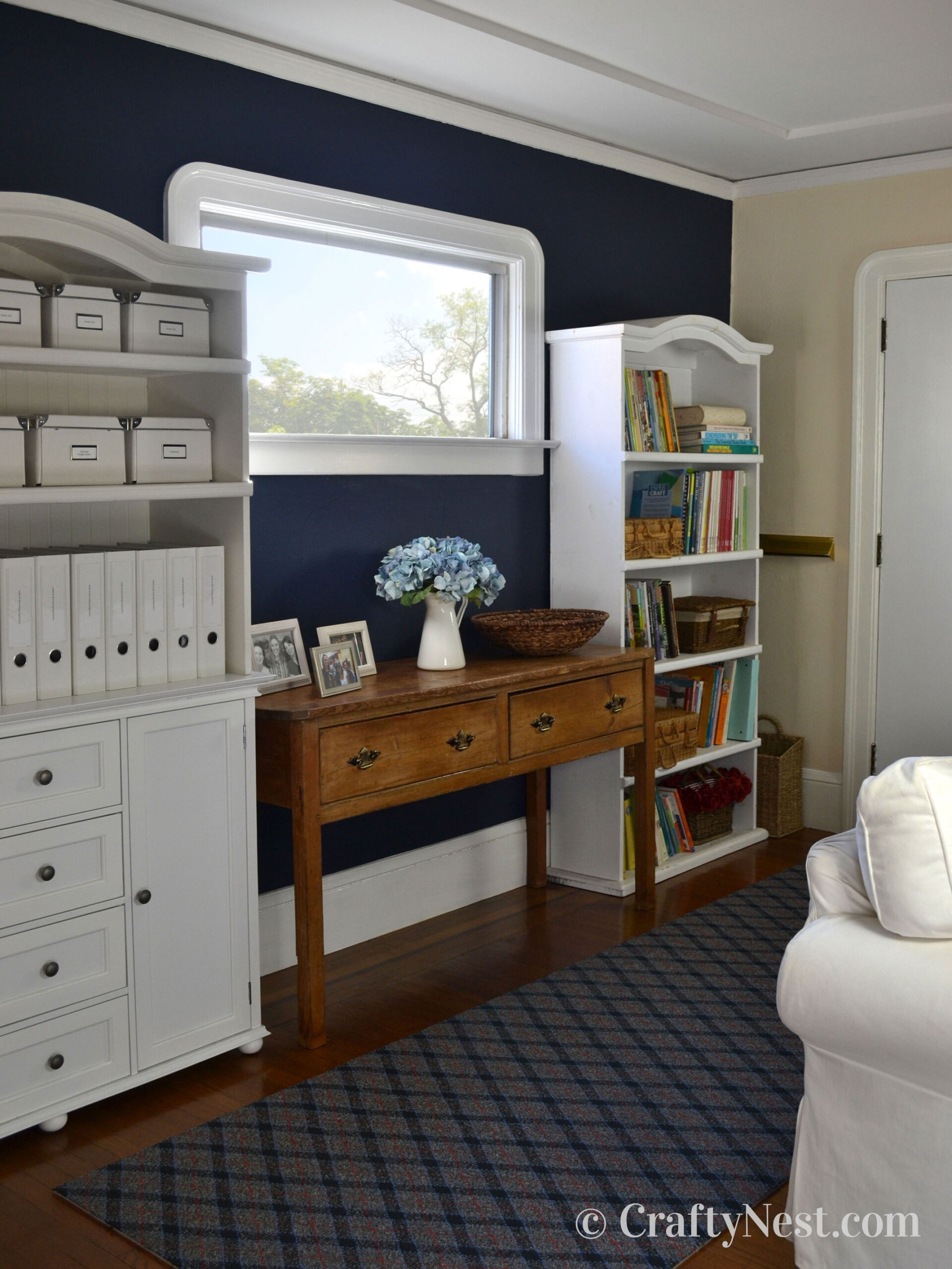 Navy blue wall with window and white bookshelves, photo