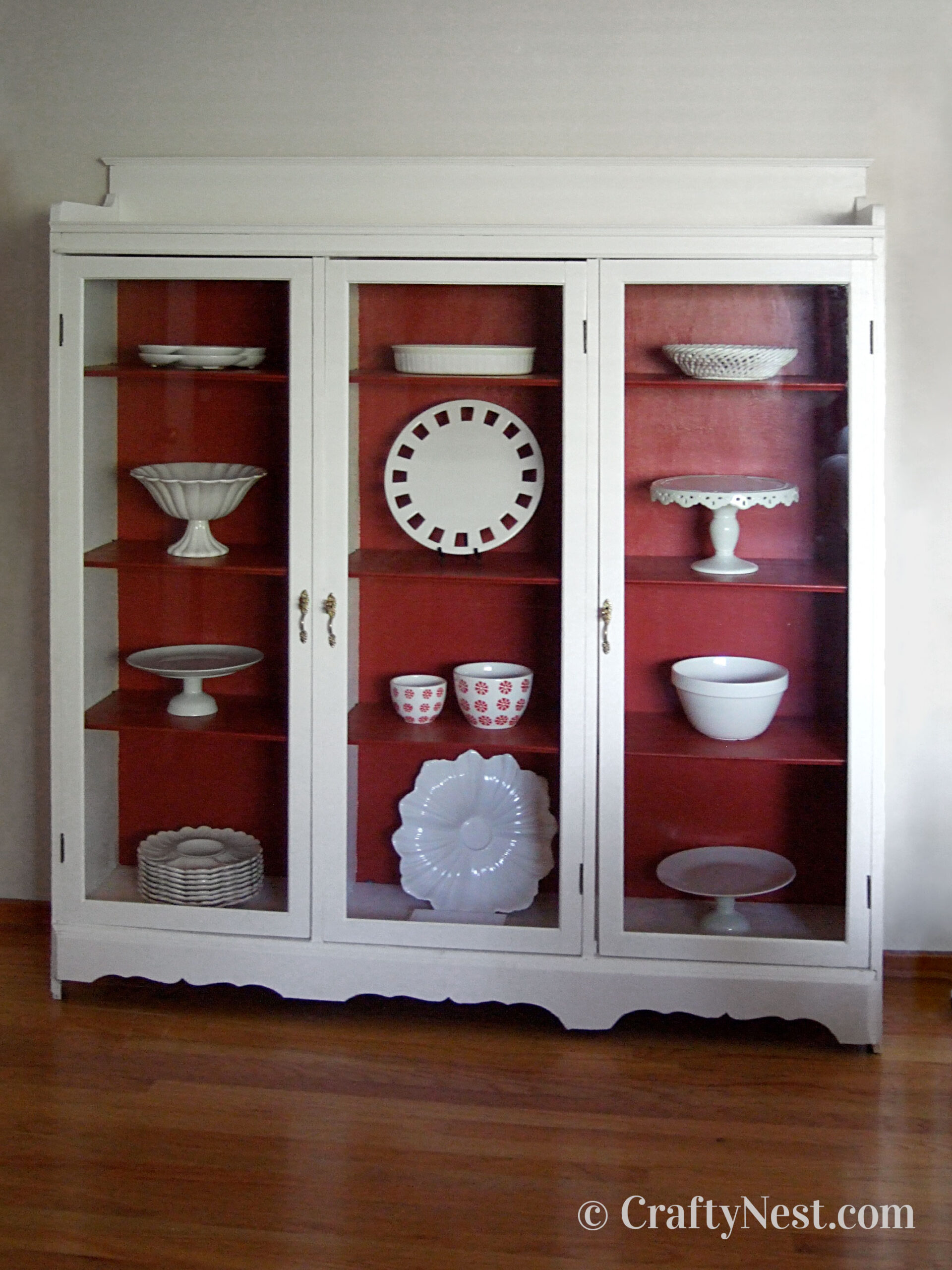 Red and white bookshelf with glass doors and white dishes inside, photo