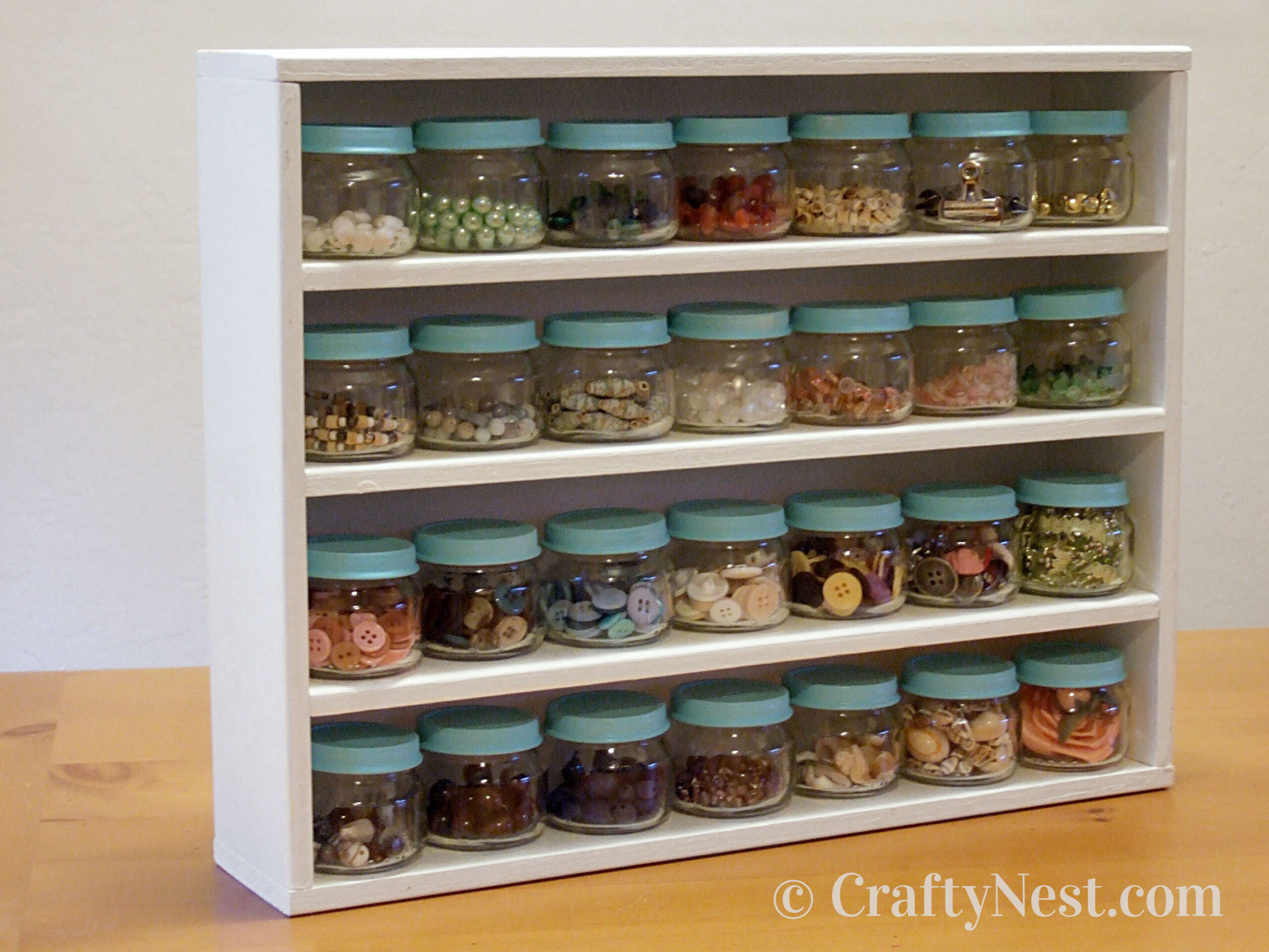 Wooden rack with baby-food jars filled with odds and ends, photo