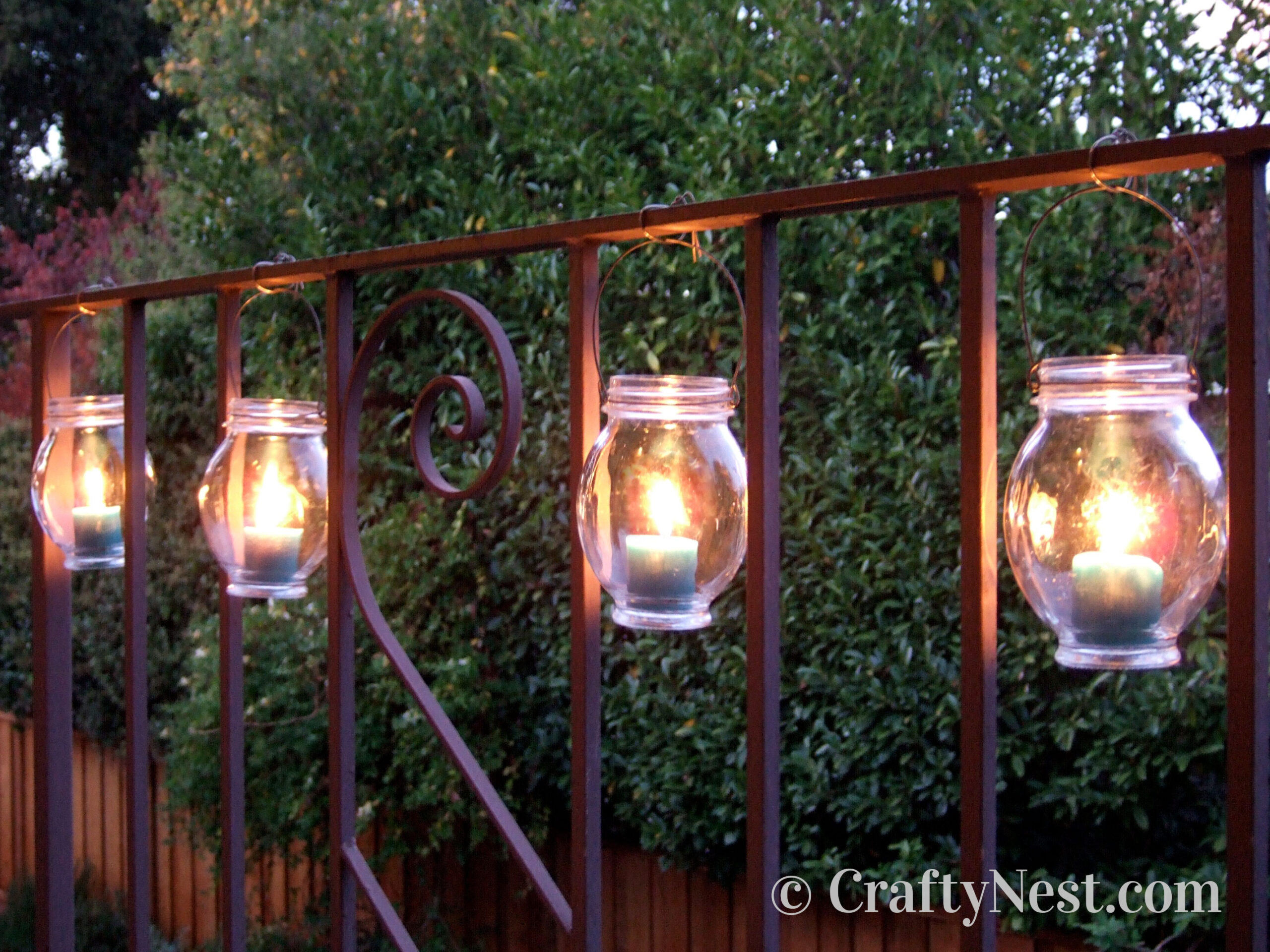 Jars with candles hanging from wire attached to a railing, photo