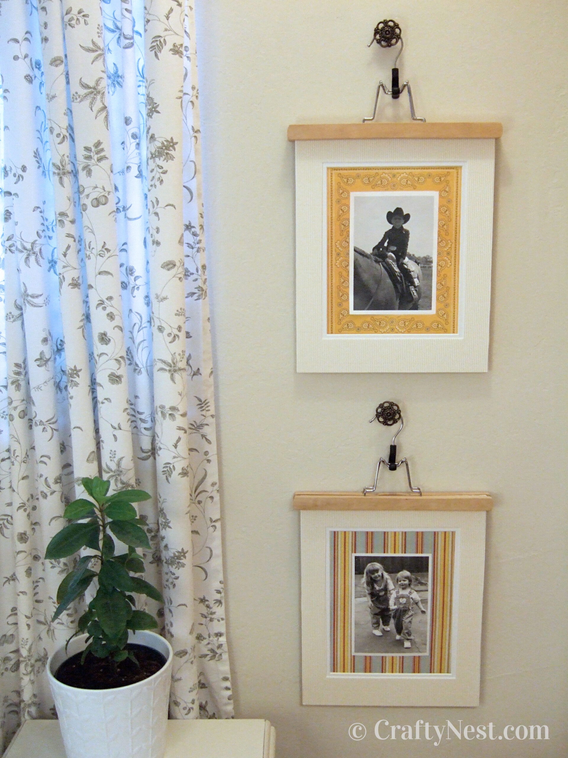 Pictures hanging from pants hangers and drawer pulls, photo