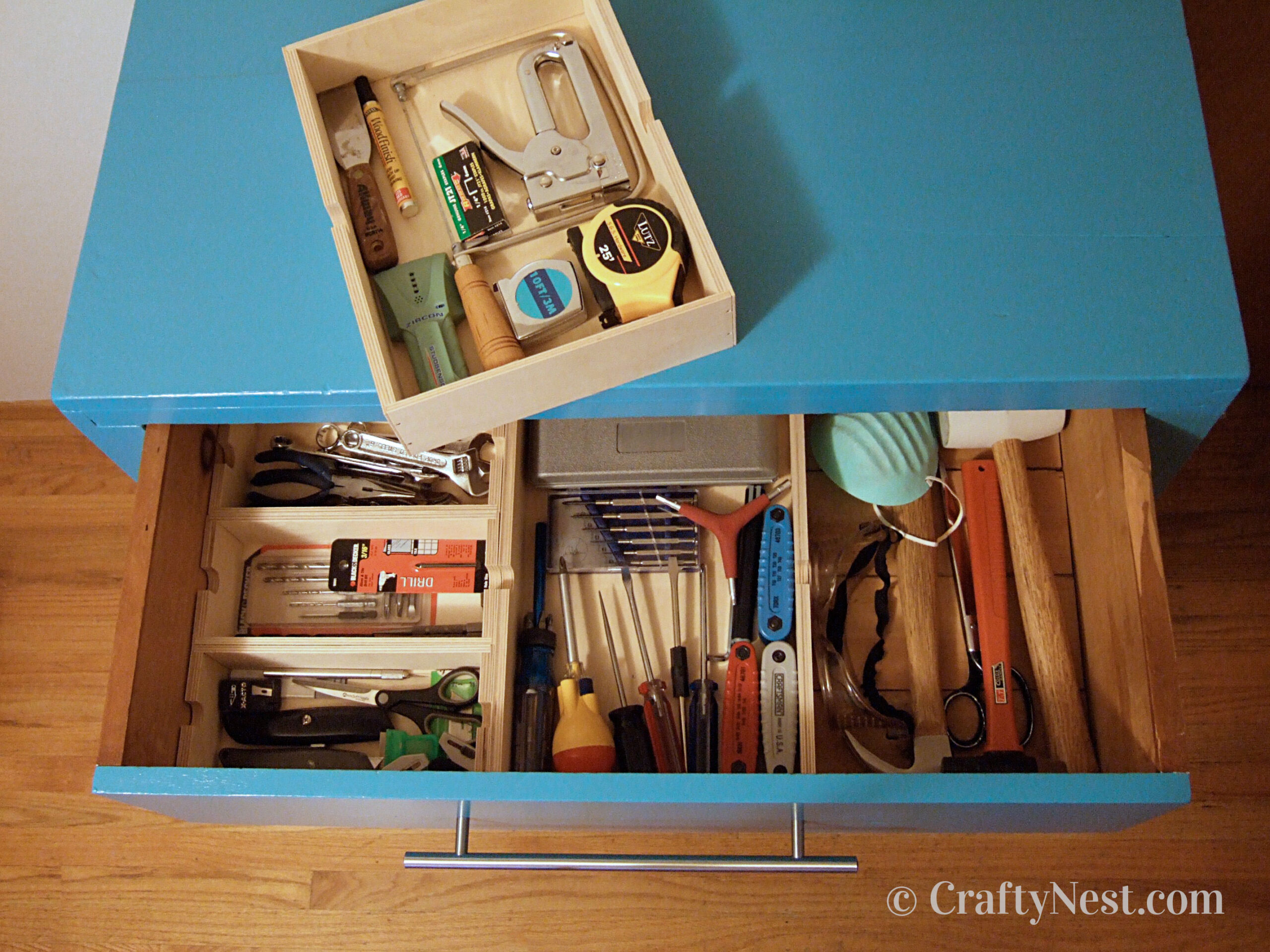 Open drawer with tools organized inside, photo