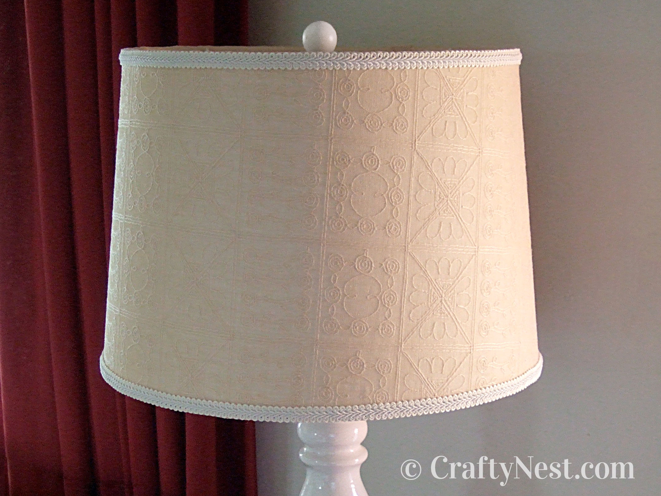 Fabric-covered lampshade on a lamp with a round white finial, photo