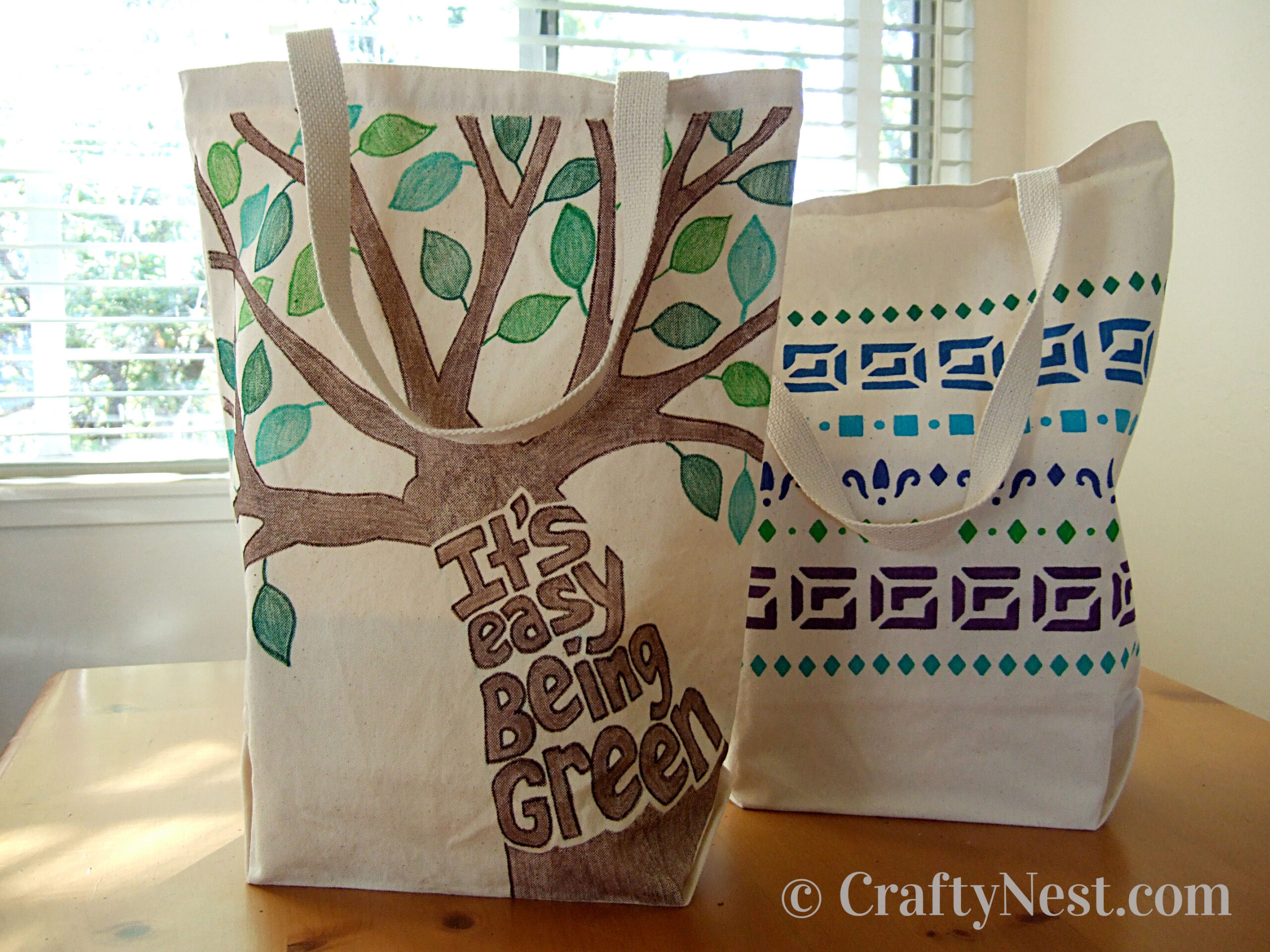 Two canvas tote bags with paint marker designs, photo