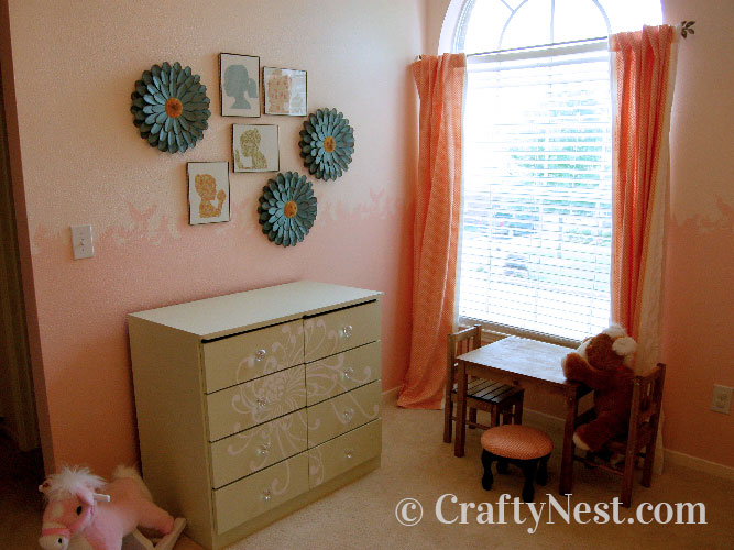 Little girl's room with stenciled walls and dresser, plus framed paper silhouettes on the wall, photo