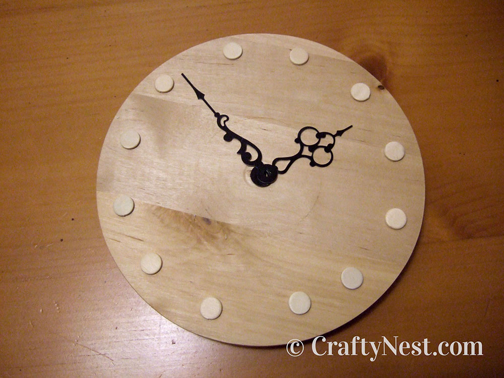 Wooden shapes places on small clock face, photo