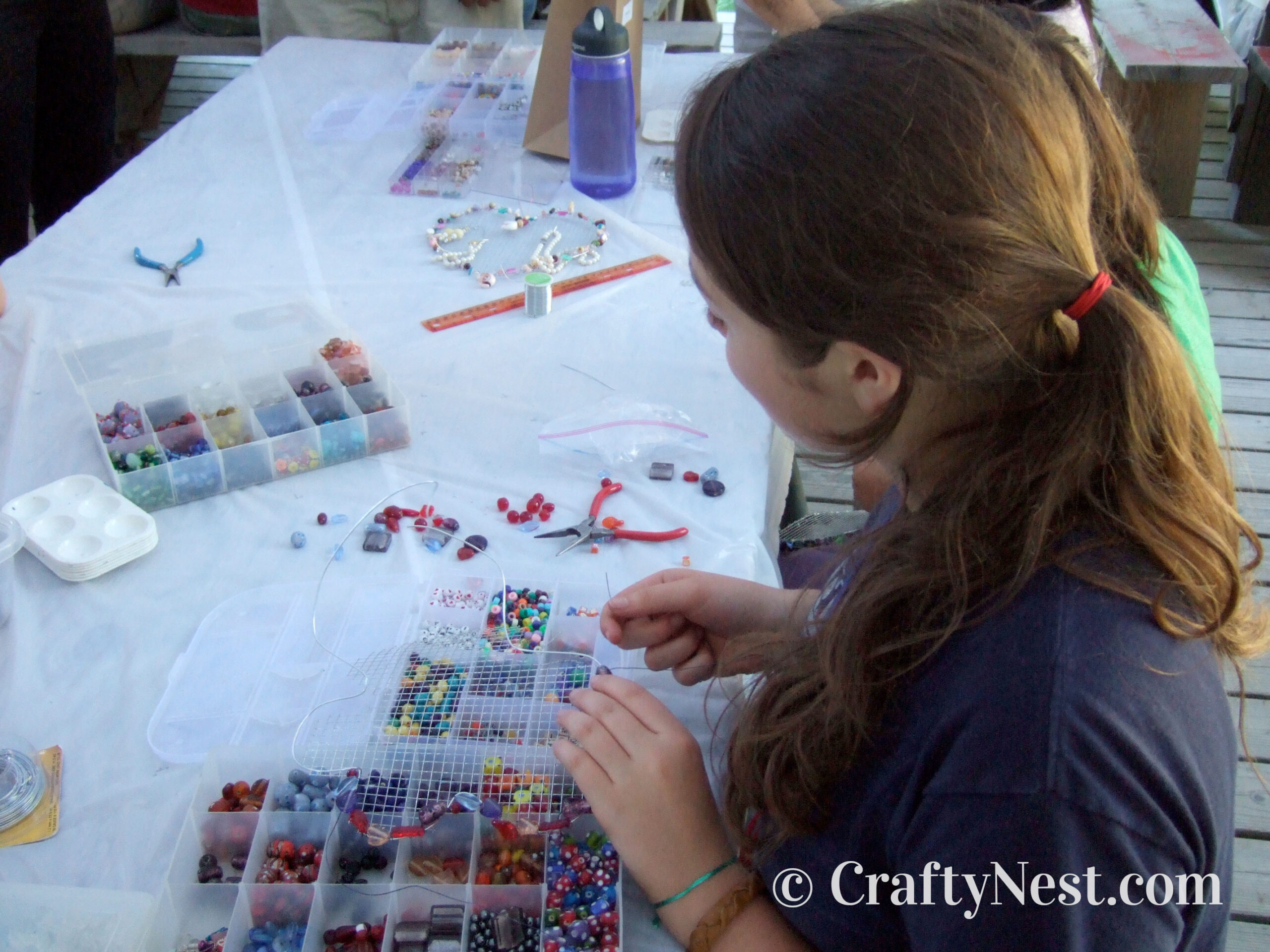 Girls making wire jewelry holders, photo