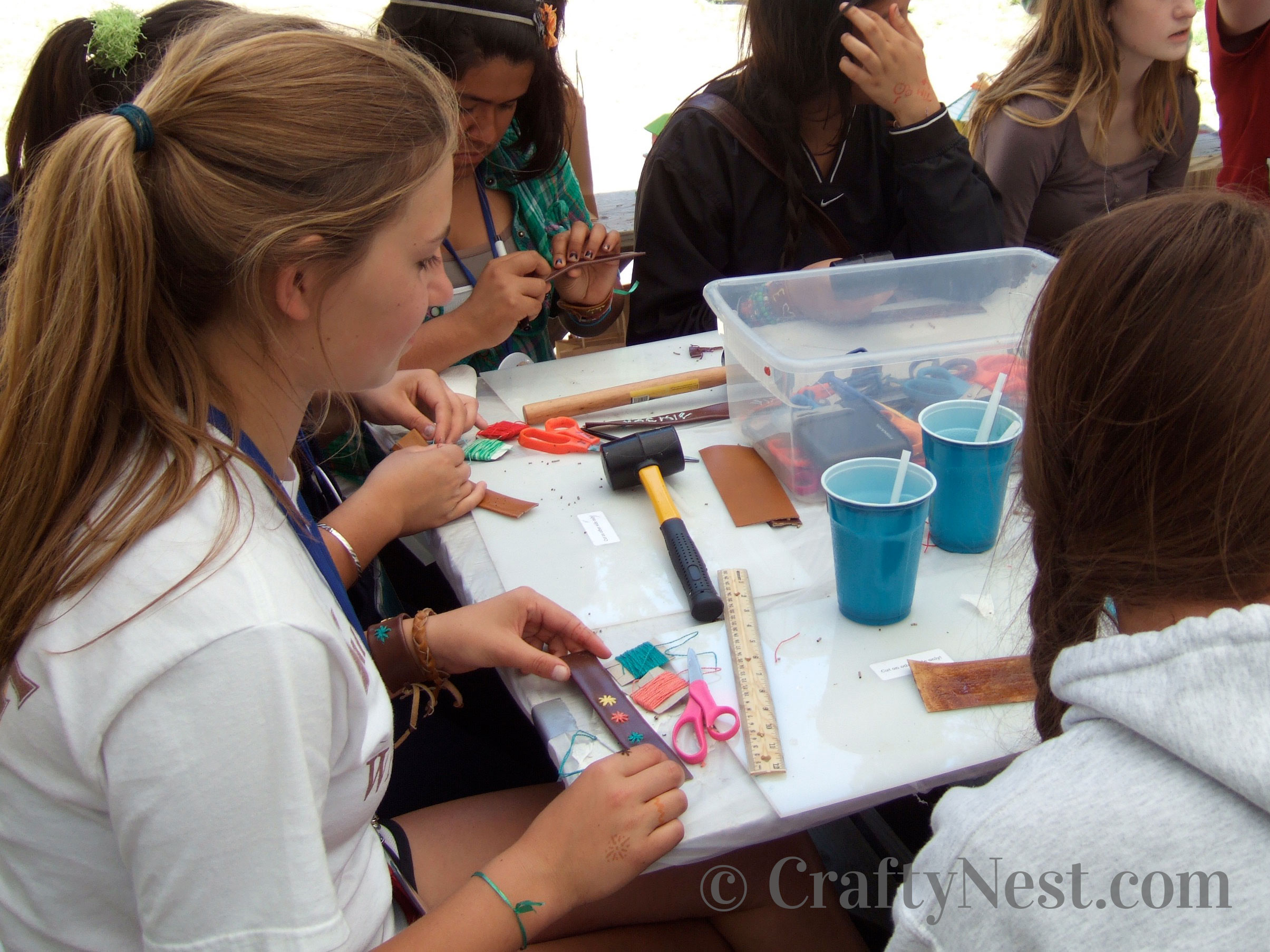 Girls making bracelets at camp, photo