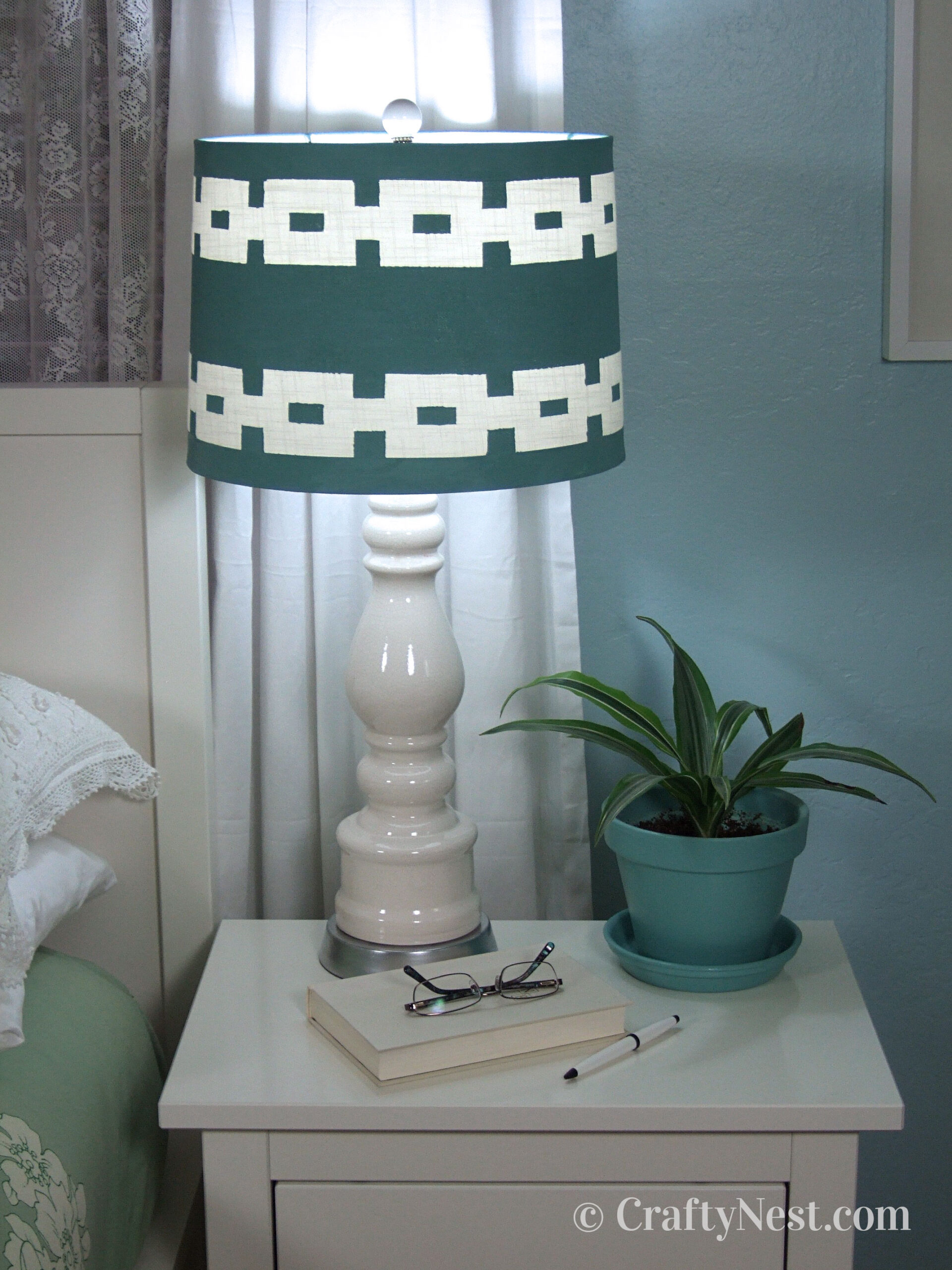 Painted lampshade, lamp with light on, and finial, photo
