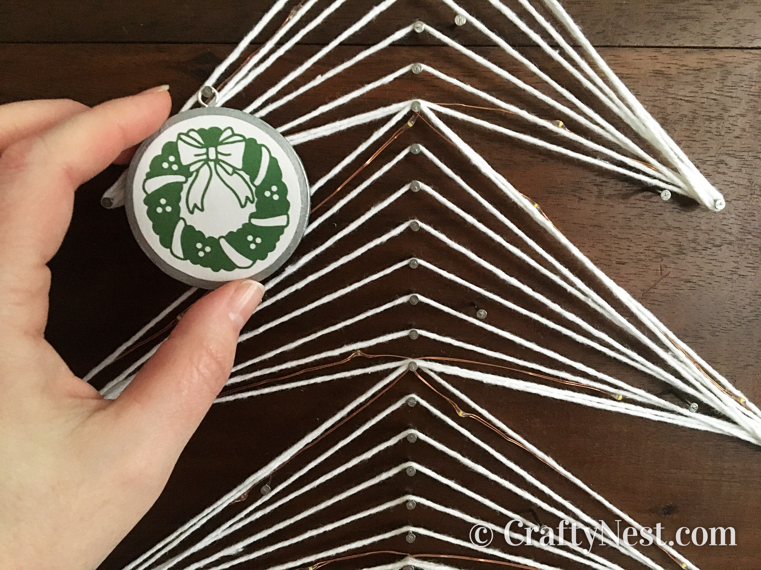 Hanging an ornament on the string-art tree, photo