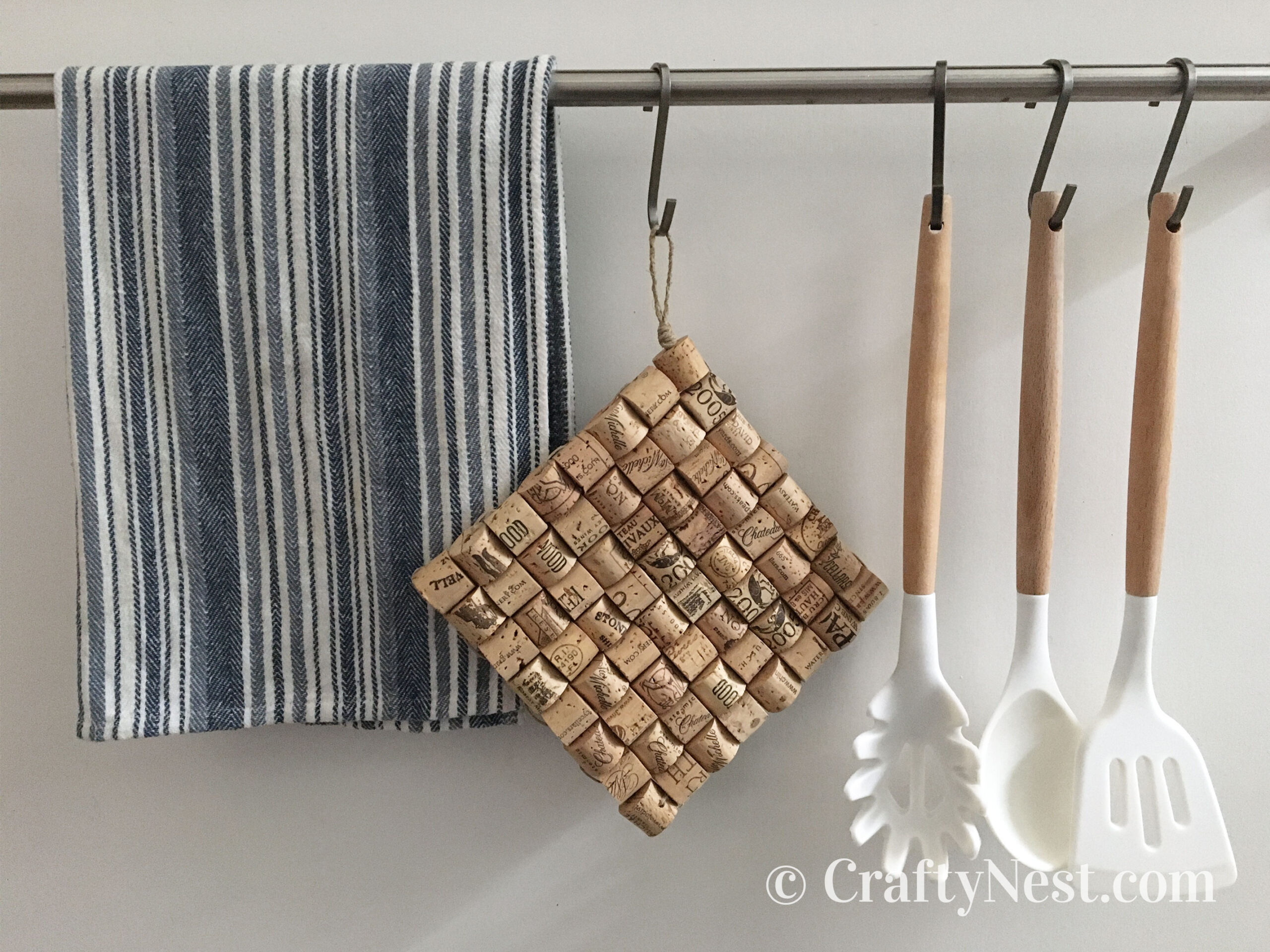 Wine-cork trivet hanging from a hook with a dish towel and cooking utensils, photo