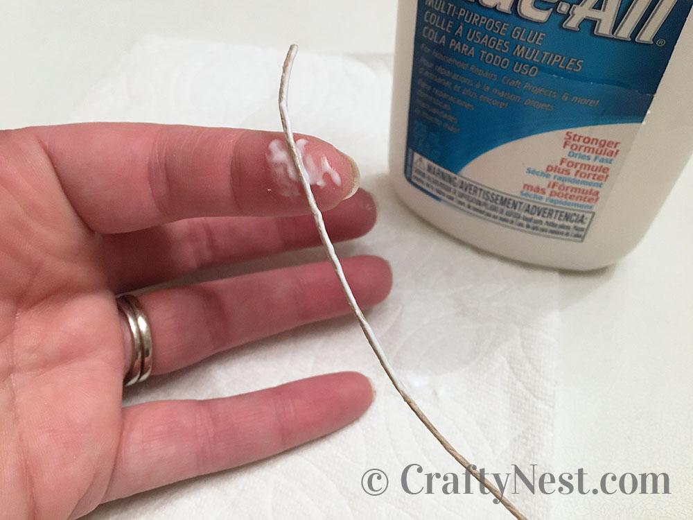 Applying glue to the hemp string, photo