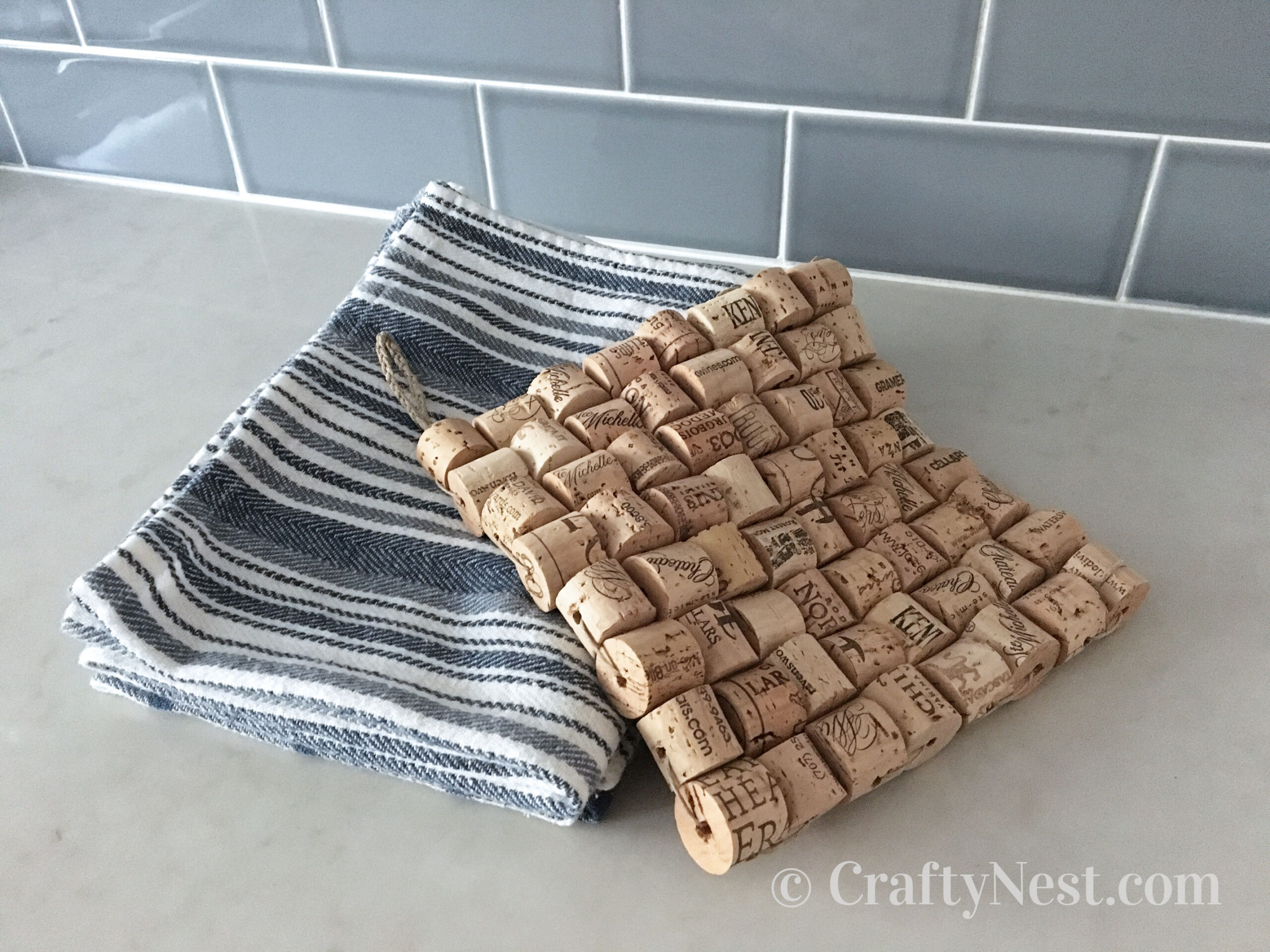 Wine cork trivet draped over a stack of dish towels, photo